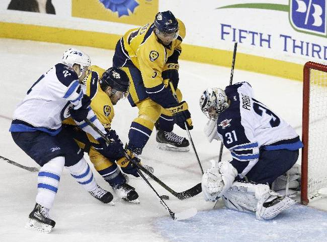 Winnipeg Jets goalie Ondrej Pavelec (31), of the Czech Republic,  makes a stop on a shot by Nashville Predators defenseman Seth Jones (3) as Jets defenseman Grant Clitsome (24) and Predators forward Mike Fisher (12) close in during the third period of an NHL hockey game on Thursday, Oct. 24, 2013, in  Nashville, Tenn. The Predators won 3-2 in overtime