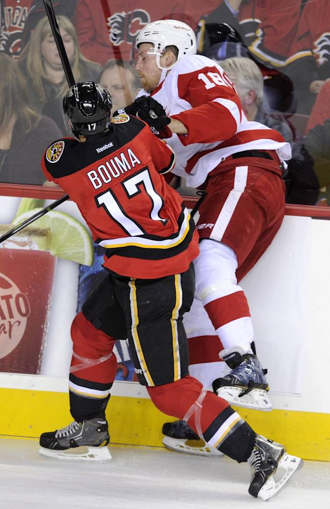Detroit Red Wings' Joakim Andersson, right, from Sweden, is checked into the boards by Calgary Flames' Lance Bouma during the first period of an NHL hockey game Friday, Nov. 1, 2013, in Calgary, Alberta