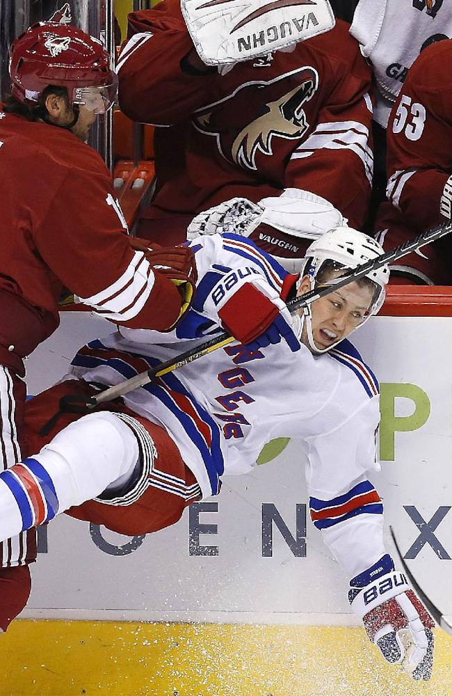 Phoenix Coyotes' Martin Hanzal, of the Czech Republic, left, checks New York Rangers' Derek Stepan into the boards in the third period during an NHL hockey game on Thursday, Oct. 3, 2013, in Glendale, Ariz.  The Coyotes defeated the Rangers 4-1