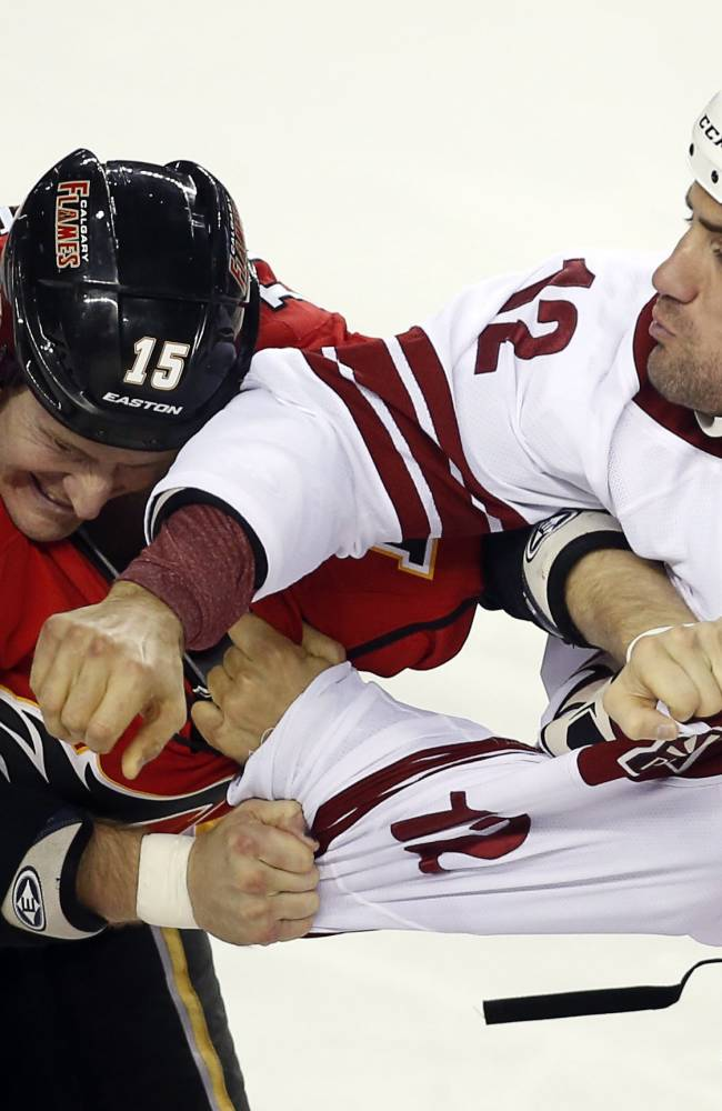 Phoenix Coyotes' Paul Bissonnette, right, fights with Calgary Flames' Tim Jackman during the third period of an NHL preseason hockey game, Wednesday, Sept. 25, 2013, in Calgary, Alberta. The Coyotes won 3-2