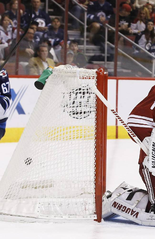 Phoenix Coyotes' Thomas Greiss (1), of Germany, gives up a goal to Winnipeg Jets' Andrew Ladd as Jets' Michael Frolik (67), of the Czech Republic, skates behind the net during the first period of an NHL hockey game, Tuesday, April 1, 2014, in Glendale, Ariz