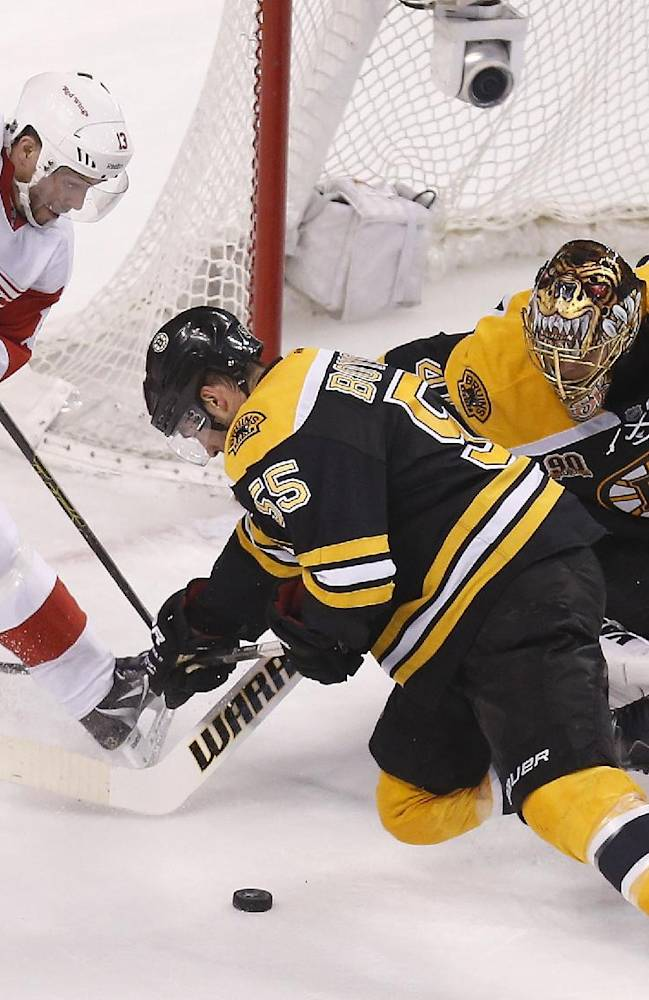 Boston Bruins' Tuukka Rask (40) and Johnny Boychuk (55) try to clear the puck away from Detroit Red Wings' Pavel Datsyuk (13) during the third period in Game 5 in the first round of the NHL hockey Stanley Cup playoffs in Boston, Saturday, April 26, 2014. Boston won 4-2 and eliminated the Red Wings from the playoffs