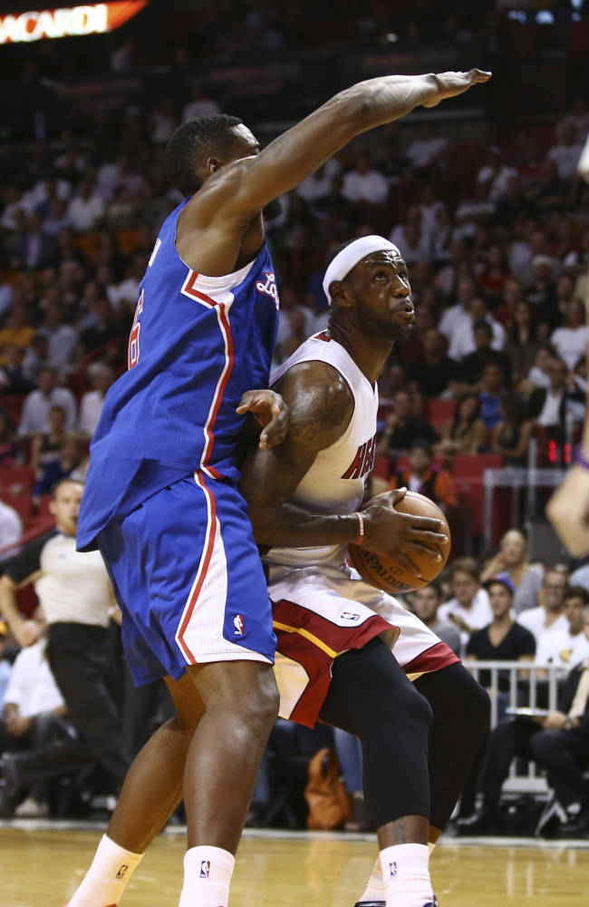 Los Angeles Clippers' DeAndre Jordan, left, blocks Miami Heat's LeBron James during the first half of an NBA basketball game in Miami, Thursday, Nov. 7, 2013