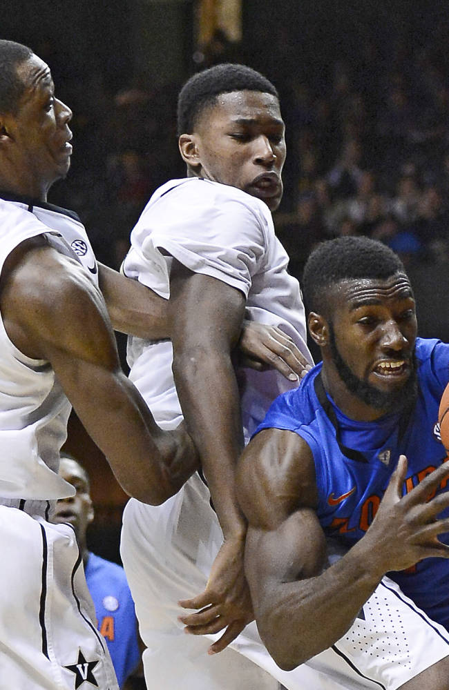 Florida center Patric Young (4), right, pulls down a rebound in front of Vanderbilt forward Rod Odom (0) and forward Damian Jones, center, in the second half of an NCAA college basketball game on Tuesday, Feb. 25, 2014, in Nashville, Tenn. Florida won 57-54