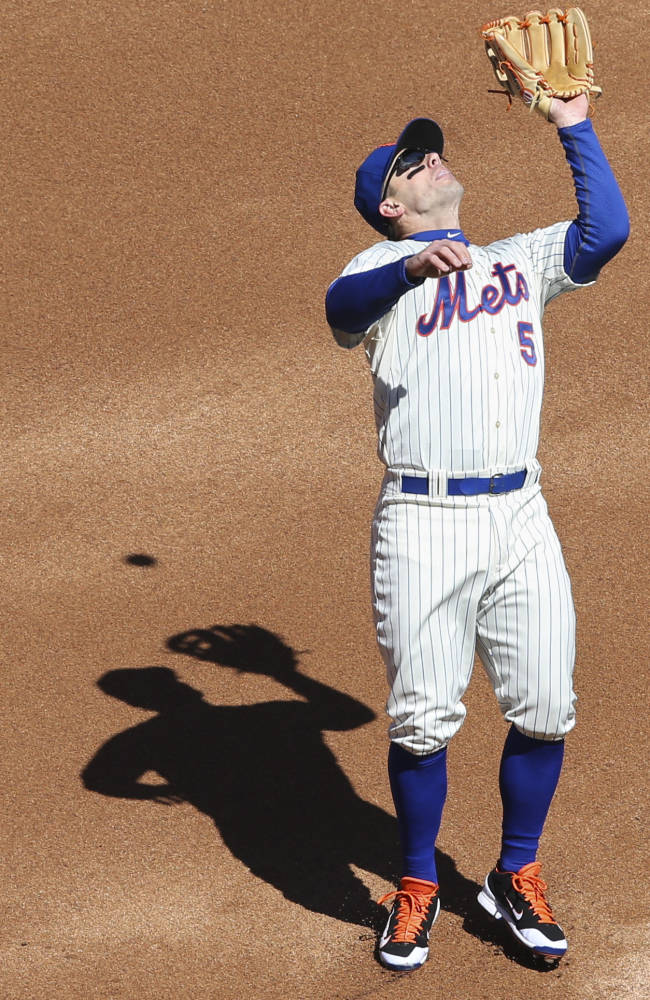 New York Mets third baseman David Wright catches a fly ball for an out in the first inning of  a baseball game against the Washington Nationals on opening day at Citi Field, Monday, March 31, 2014, in New York