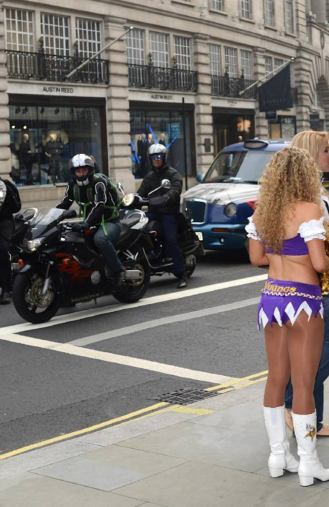 In this image made available by the NFL, Minnesota Vikings cheerleaders stand in London's Regent Street , watched by passing traffic, during an arranged photo shoot, Wednesday, Sept. 25, 2013. The Minnesota Vikings will play the Pittsburgh Steelers at London's Wembley Stadium on Sunday