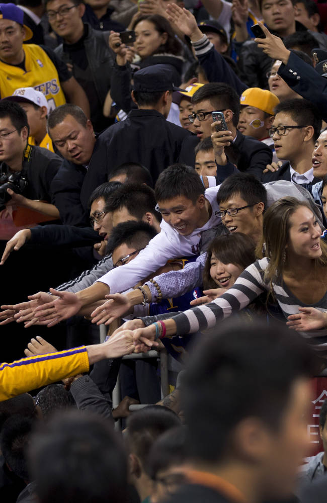 Chinese fans shake hand with Pau Gasol of the LA Lakers after the NBA Global Game with Golden State Warriors at the Wukesong Stadium in Beijing, Tuesday, Oct. 15, 2013. The Warriors defeated Lakers 100-95