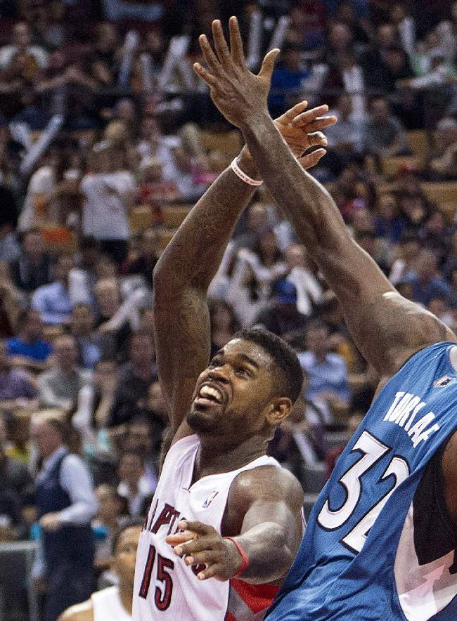 Toronto Raptors forward Amir Johnson, left, looses the ball against Minnesota Timberwolves center Ronny Turiaf (32) during the first half of an NBA preseason basketball game in Toronto on Wednesday, Oct. 9, 2013