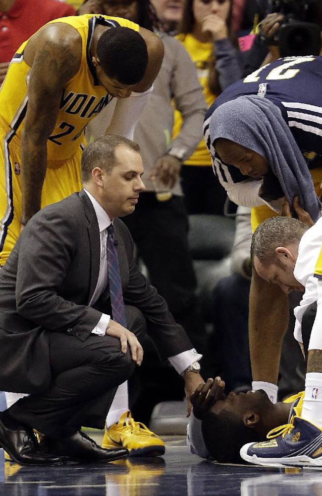 In this Wednesday, March 26, 2014 photo, Indiana Pacers head coach Frank Vogel and other members of the team attend to Pacers center Roy Hibbert (55) after he was struck in the face by an elbow from Miami Heat forward LeBron James (6), which was ruled a flagrant fou,  during the second half of an NBA basketball game in Indianapolis. The Pacers won 84-83. It was the rare grudge match that actually lived up to its billing. Before the game, the teams chided one another with dueling comments. Afterward, nobody was ready to make up. And in between, the action got downright nasty