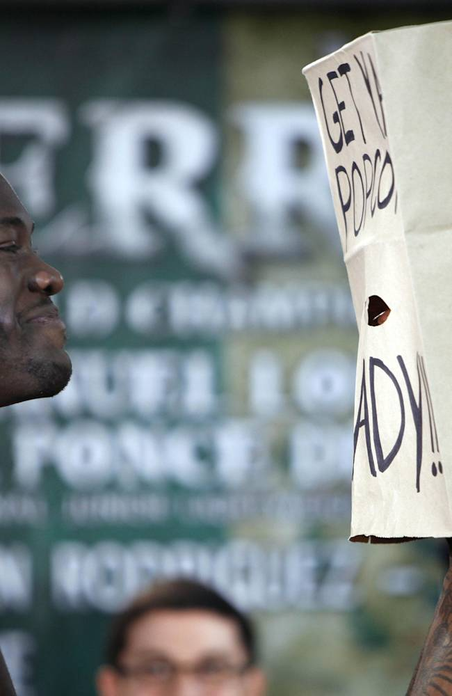 WBC Continental Americas Heavyweight Champion Deontay Wilder, left, and contender Malik Scott, wearing a mask made from a paper bag with a message that reads; Get ya popcorn ready!!,