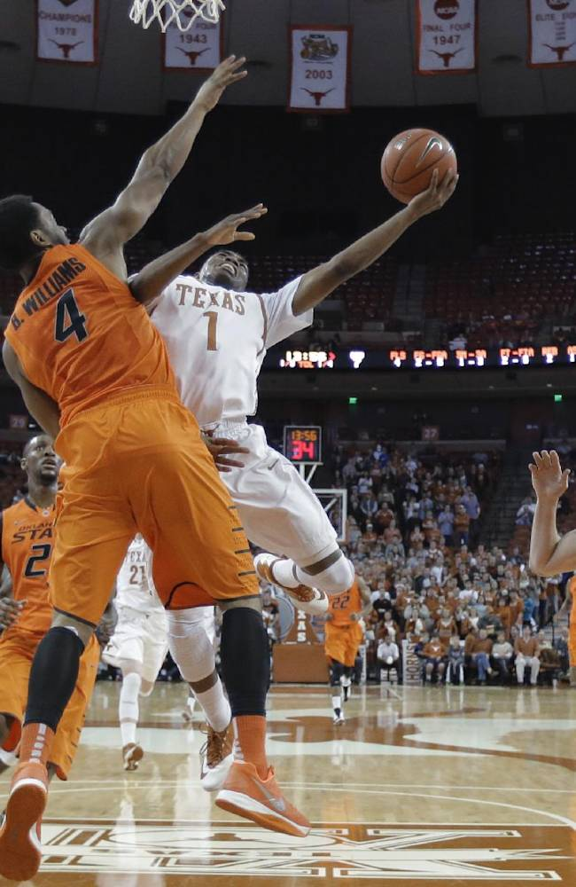Texas' Isaiah Taylor (1) drives against Oklahoma State's Brian Williams (4) during the first half on an NCAA college basketball game, Tuesday, Feb. 11, 2014, in Austin, Texas