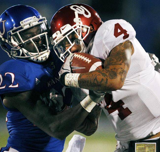 In this Oct. 15, 2011, file photo, Oklahoma wide receiver Kenny Stills (4) is tackled by Kansas cornerback Dexter McDonald (22) during the first half of an NCAA college football game in Lawrence, Kan. Darrian Miller and McDonald are grateful to have a second chance. Kicked off the Kansas football team by coach Charlie Weis, they spent last season at a junior college, and have now worked their way back into the Jayhawks' program