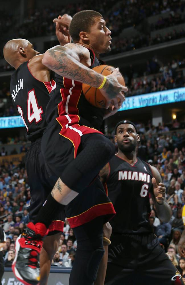 Miami Heat forward Michael Beasley, front, muscles a rebound away from teammate Ray Allen, middle, as forward LeBron James, back looks on against the Denver Nuggets in the fourth quarter of the Heat's 97-94 victory in an NBA basketball game in Denver on Monday, Dec. 30, 2013