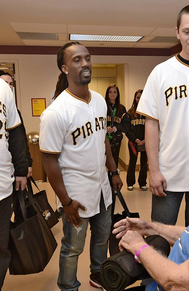 Pittsburgh Pirates baseball players, from left, pitcher Bryan Morris, center fielder Andrew McCutchen and pitcher Jared Hughes meet patient Ed Detrick, of Conneaut, Ohio, at Saint Vincent Hospital in Erie, Pa., Thursday, Dec. 12, 2013. The players spent Thursday morning visiting patients and employees at the hospital as part of the team's annual caravan fan tour