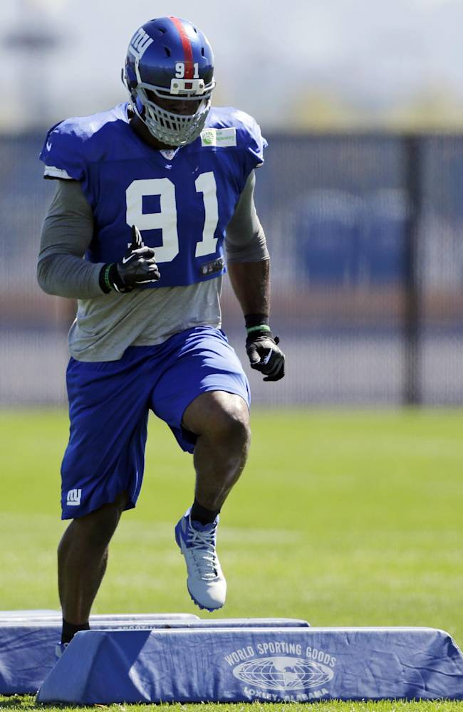 In this photo taken Wednesday, Sept. 18, 2013,  New York Giants defensive end Justin Tuck works out during NFL football practice in East Rutherford, N.J. Two weeks into the season, the Giants are still looking for a pass rush. The defensive line will have another chance on Sunday, when they travel to face the Carolina Panthers