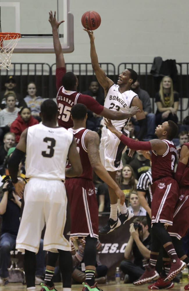 Massachusetts forward Cady Lalanne (25) soars to block the shot of St. Bonaventure guard Andell Cumberbatch during the first half  of an NCAA college basketball game in St. Bonaventure, N.Y., Wednesday, Jan. 29, 2014