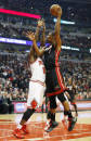 Miami Heat center Chris Bosh, right, shoots over Chicago Bulls forward Luol Deng, left, during the first half of an NBA basketball game in Chicago, Thursday, Dec. 5, 2013. (AP Photo/Kamil Krzaczynski)