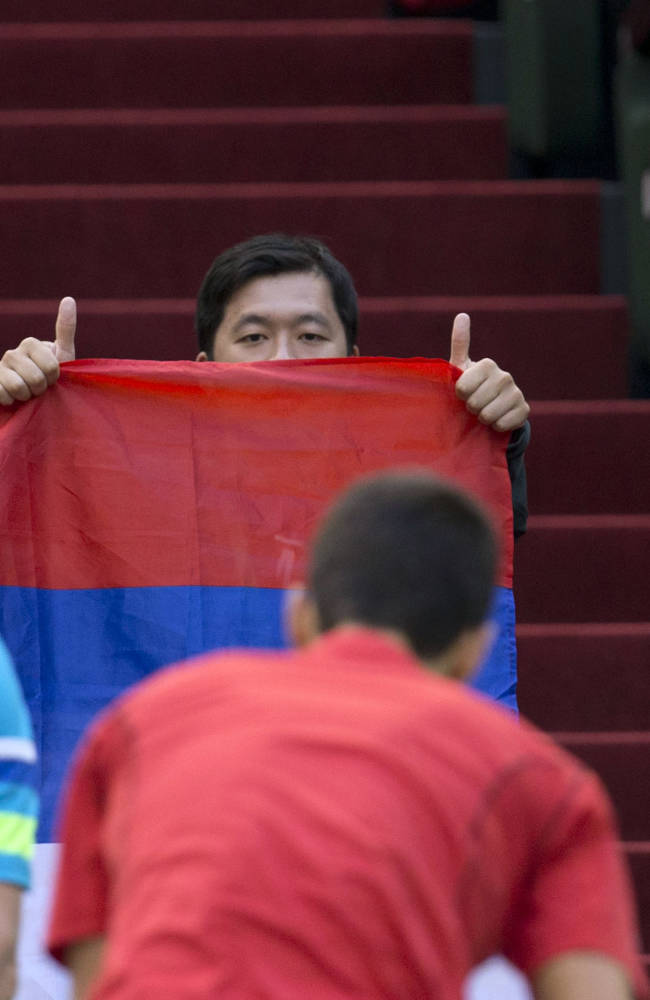 A fan of Serbia's Novak Djokovic holds up the Serbian flag while giving two thumbs up to the Serbian before a match against Spain's Marcel Granollers for the Shanghai Masters tennis tournament at the Qizhong Forest Sports City Tennis Center in Shanghai, China, Wednesday, Oct. 9, 2013. Djokovic won 6-2, 6-0