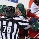Linesman Brian Mach tries to break up an altercation as Minnesota Wild's Zach Parise, left, and Jared Spurgeon, right, take on Columbus Blue Jackets' Matt Calvert, center with face showing, in the third period of an NHL hockey game, Monday, Jan. 19, 2015,