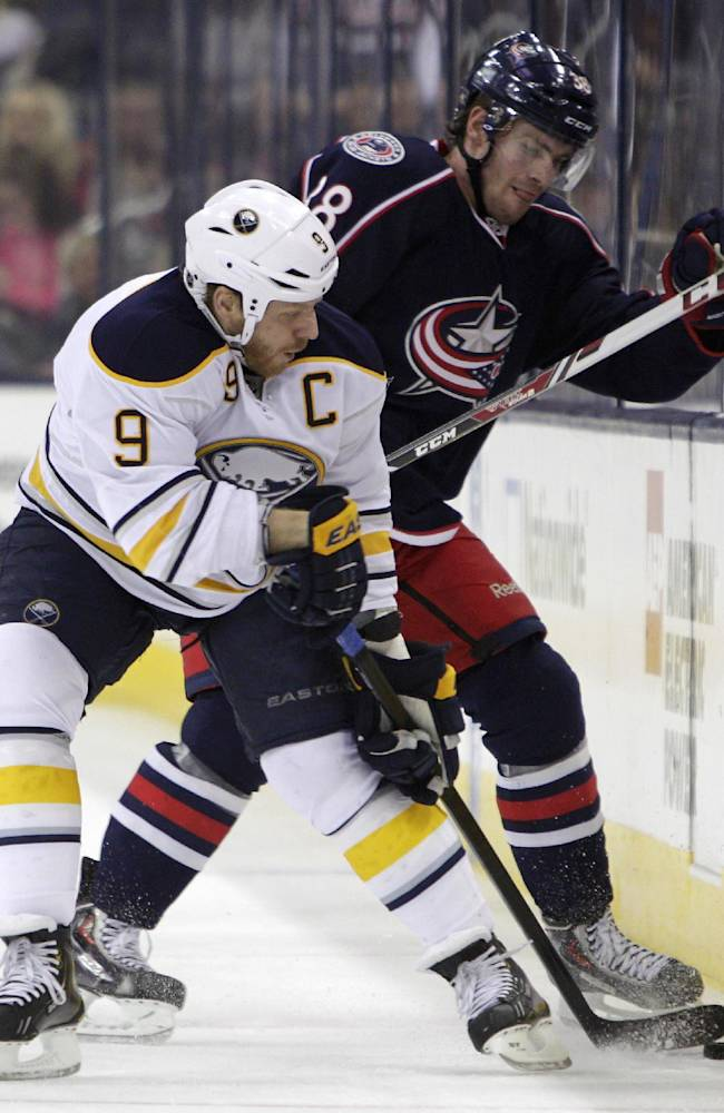 Buffalo Sabres' Steve Ott, left, and Columbus Blue Jackets' Boone Jenner fight for a loose puck during the first period of an NHL hockey game, Saturday, Jan. 25, 2014, in Columbus, Ohio