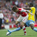 Arsenal's Mathieu Debuchy, left, fights for the ball with Crystal Palace's Yannick Bolasie, during their English Premier League soccer match at Emirates Stadium, in London, Saturday, Aug. 16, 2014