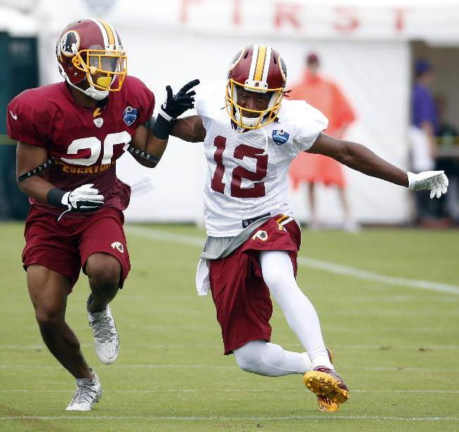 Washington Redskins receiver Andre Roberts (12) plants his foot to try to avoid coverage by cornerback Richard Crawford during practice at the team's NFL football training facility, Sunday, July 27, 2014 in Richmond, Va