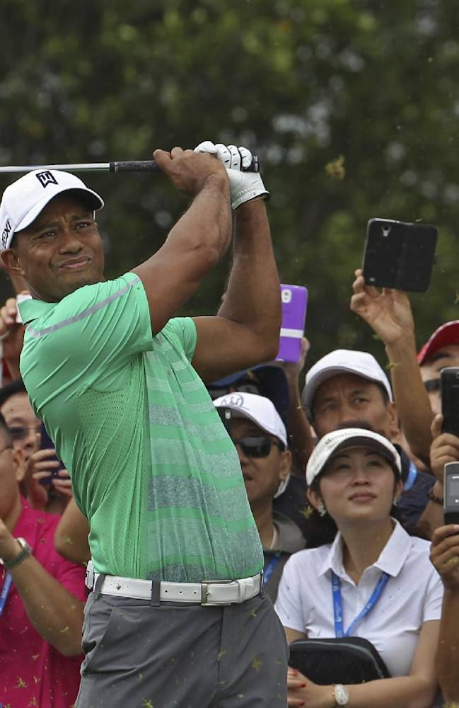 Tiger Woods of the United States tees off during an exhibition golf match against Rory Mcllory of Northern Ireland in Haikou, in southern China's island province Hainan, Monday, Oct. 28, 2013
