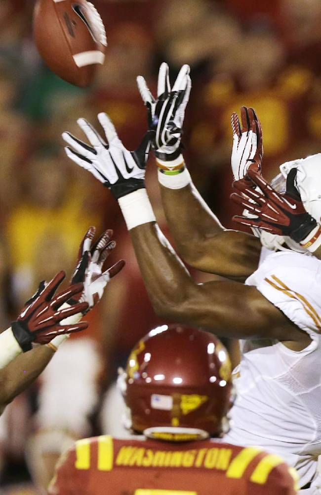 Texas tight end John Harris (9) catches a 44-yard touchdown pass over Iowa State's Jeremiah George (52) and Deon Broomfield (26) during the first half of an NCAA college football game on Thursday, Oct. 3, 2013, in Ames, Iowa