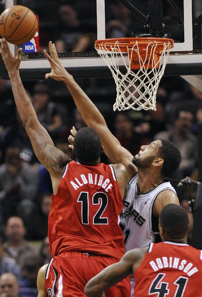 In this March 12, 2014 file photo, San Antonio Spurs forward Tim Duncan, right rear, defends Portland Trailblazers forward LaMarcus Aldridge, left, as Portland Trailblazers forward Thomas Robinson looks on, during the first half of an NBA basketball game in San Antonio. The Western Conference semifinal battle between San Antonio and Portland begins Tuesday, May 6, 2014, in San Antonio