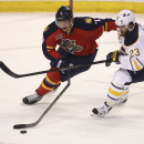 Florida Panthers' Dmitry Kulikov (7) breaks his stick while he and Buffalo Sabres' Ville Leino (23) chase the puck during the second period of an NHL hockey game in Sunrise, Fla., Friday, March 7, 2014 The Associated Press