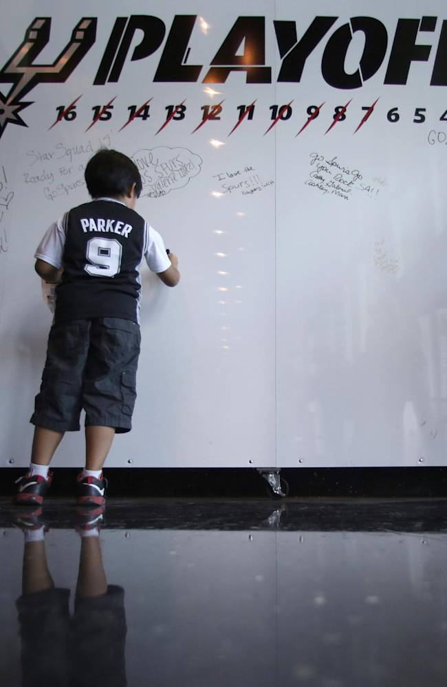 San Antonio Spurs fans sign a message board at the AT&T Center prior to Game 5 of the Western Conference finals NBA basketball playoff series between the Spurs and the Oklahoma City Thunder, Thursday, May 29, 2014, in San Antonio