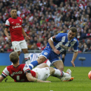 Wigan Athletic's Callum McManaman, right, is tackled down by Arsenal's Per Mertesacker which resulted in a penalty during their English FA Cup semifinal soccer match at Wembley Stadium in London, Saturday, April 12, 2014