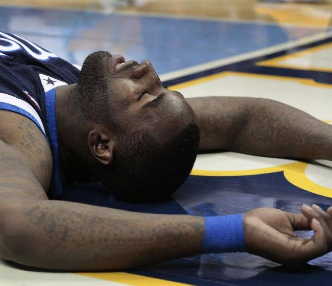 Dallas Mavericks center DeJuan Blair (45) lays on the floor after committing a foul during the fourth quarter of an NBA basketball game against the Denver Nuggets in Denver on Saturday, Nov. 23, 2013. Denver won, 102-100