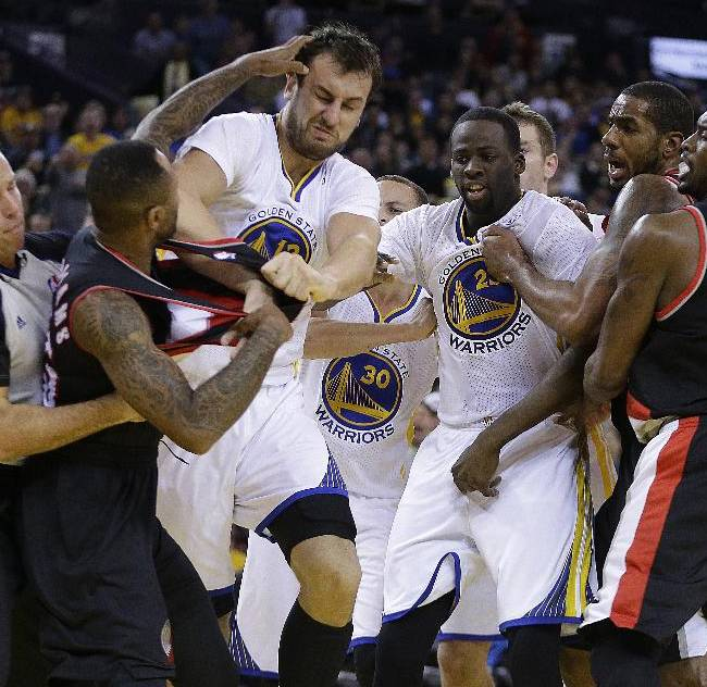 Portland Trail Blazers' Mo Williams, left, is restrained by a referee, left, as he fights with Golden State Warriors' Andrew Bogut (12) during the second half of an NBA basketball game Saturday, Nov. 23, 2013, in Oakland, Calif. Trail Blazers Wesley Matthews, Mo Williams, and Warriors' Draymond Green were ejected from the game