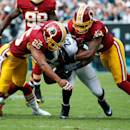 Philadelphia Eagles' LeSean McCoy (25) is tackled by Washington Redskins' Ryan Clark, left, and David Amerson, right, during the first half of an NFL football game against the Washington Redskins, Sunday, Sept. 21, 2014, in Philadelphia The Associated Pre