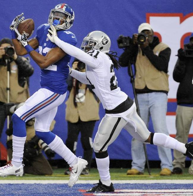 New York Giants wide receiver Rueben Randle, left, catches a touchdown pass as Oakland Raiders cornerback Mike Jenkins (21) defends on the play during the first half of an NFL football game on Sunday, Nov. 10, 2013, in East Rutherford, N.J