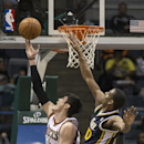 Milwaukee Bucks' Ersan Ilyasova, left, puts up a reverse layup over Utah Jazz Alec Burks during the second half of an NBA basketball game Monday, March 3, 2014, in Milwaukee The Associated Press