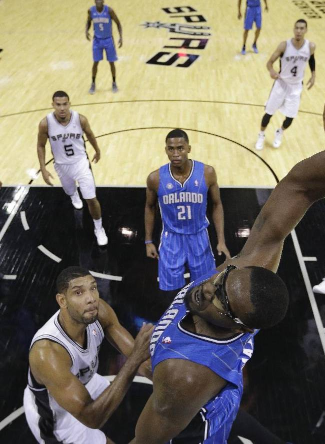 Orlando Magic's Jason Maxiell, right, dunks the ball over San Antonio Spurs' Tim Duncan, left, during the first half of a preseason NBA basketball game, Tuesday, Oct. 22, 2013, in San Antonio