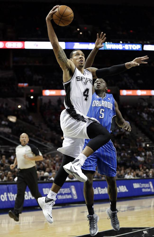 San Antonio Spurs' Danny Green (4) drives past Orlando Magic's Victor Oladipo to score during the first half of a preseason NBA basketball game, Tuesday, Oct. 22, 2013, in San Antonio