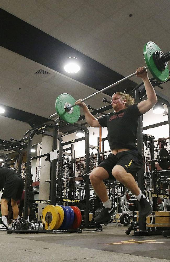 Arizona State football players lift weights in the Arizona State football training room on Monday, July 21, 2014, in Tempe, Ariz