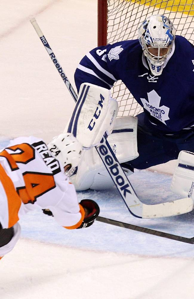 Philadelphia Flyers' Matt Read stretches to try and get the puck behind Maple Leafs' goalie Christopher Gibson during the third period of an NHL pre-season game, Sunday Sept. 15, 2013 in London, Ontario