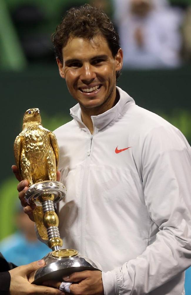 Spain's Rafael Nadal poses with the trophy after winning the final match against France's Gael Monfils during the ExxonMobil Qatar ATP Open Tennis tournament at the Khalifa Tennis Squash Complex in Doha, Qatar, Saturday, Jan. 4, 2014