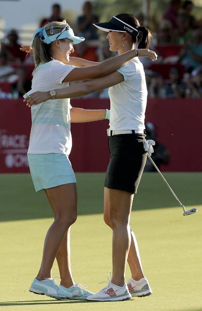 Lexi Thompson, left, hugs Michelle Wie after Thompson's three-stroke victory over Wie in the Kraft Nabisco Championship golf tournament Sunday, April 6, 2014, in Rancho Mirage, Calif