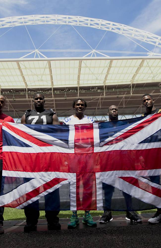 NFL players, from left, Atlanta Falcons British-born defensive end Osi Umenyiora, British-born Oakland Raiders offensive tackle Menelik Watson, Dallas Cowboys cornerback Brandon Carr, Detroit Lions linebacker Stephen Tulloch, Jacksonville Jaguars cornerback Will Blackmon and Miami Dolphins defensive end Cameron Wake pose for photographers with a Union flag at Wembley Stadium in London, Wednesday, July 16, 2014.  The six players from teams who will play in the three regular season NFL games at Wembley in the autumn were in London for media and promotional events on Wednesday