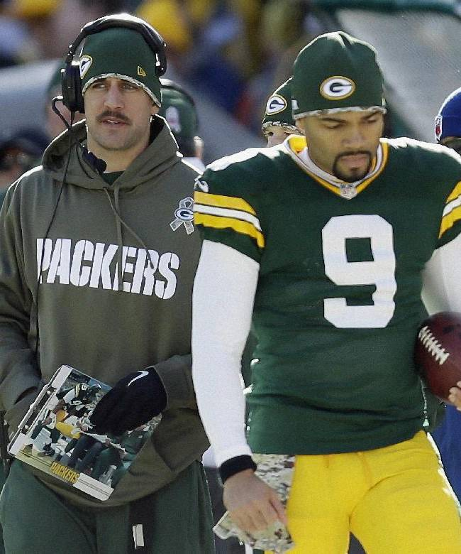 Green Bay Packers' Aaron Rodgers is seen on the sidelines with Seneca Wallace (9) during the first half of an NFL football game against the Philadelphia Eagles Sunday, Nov. 10, 2013, in Green Bay, Wis