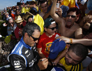 Juan Pablo Montoya, of Colombia, signs autographs for fans in the grandstand after he won the Pocono IndyCar 500 auto race, Sunday, July 6, 2014, in Long Pond, Pa. (AP Photo/Matt Slocum)