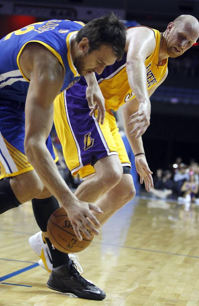 Golden State Warriors center Andrew Bogut, left, of Australia, steals the ball from Los Angeles Lakers center Chris Kaman in the first quarter during an NBA basketball preseason game Saturday, Oct. 5, 2013, in Ontario, Calif