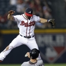 Minnesota Twins' Justin Morneau (33) is forced out at second base by Atlanta Braves second baseman Dan Uggla (26) on a Trevor Plouffe (24) ground ball in the sixth inning of a baseball game Tuesday, May 21, 2013 in  in Atlanta. (AP Photo/John Bazemore)