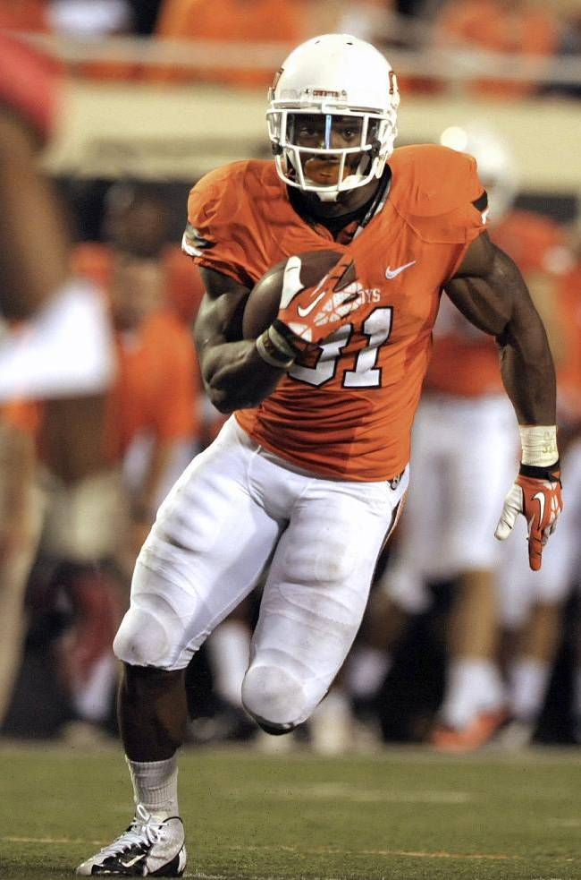 In this Sept. 14, 2013, Oklahoma State running back Jeremy Smith runs down field during an NCAA football game against Lamar in Stillwater, Okla. Smith has gone relatively unnoticed, though he shares the Big 12 lead in touchdowns. The Cowboys open conference play this weekend at West Virginia