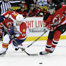 Florida Panthers' Tomas Fleischmann, left, of the Czech Republic, and New Jersey Devils' Mark Fayne chases after the puck during the first period of an NHL hockey game Monday, March 31, 2014, in Newark, N.J. The Devils won 6-3 The Associated Press